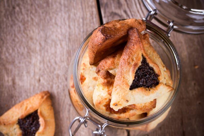 Hamantaschen cookies for Purim in glass jar stock photo