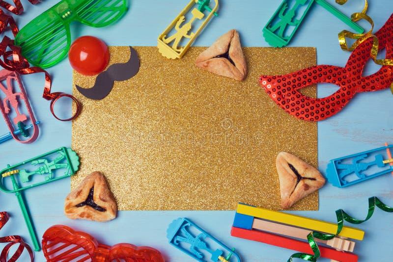Hamantaschen goldener Funkelnhintergrund Purim mit Karnevalsmaske, Parteikostüm und Plätzchen lizenzfreies stockbild