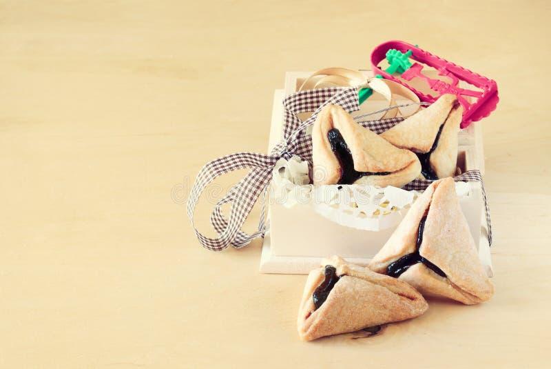 Hamantaschenkoekjes of hamans oren voor Purim-viering in houten doos en Noisemaker royalty-vrije stock foto's