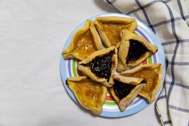 Hamantash普珥节蓝莓和杏子在套色板的果酱曲奇饼有格子花呢披肩蓝色旧布和白色板料背景的 库存照片
