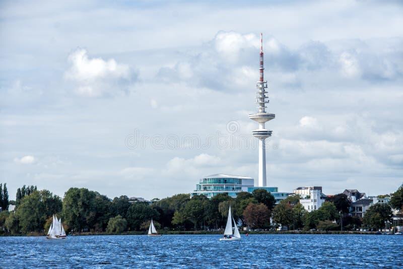Hambourg Alster avec la tour de TV sur l'horizon et les bateaux de navigation sur l'eau image stock