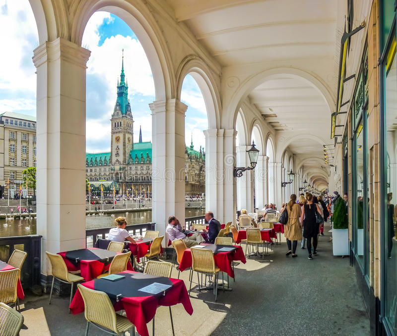 Hamburg city center with coffee shop and town hall, Germany. Beautiful view of historic ambulatories and traditional coffee shop with town hall and Alster river royalty free stock image
