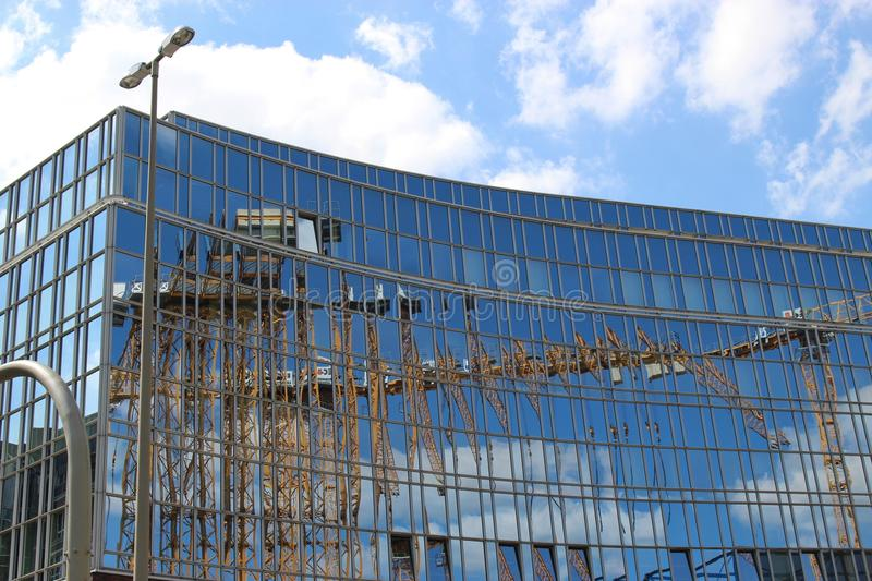 In Hamburg city center, Germany,Europe. Reflections of construction cranes on the glass front of a building royalty free stock photos