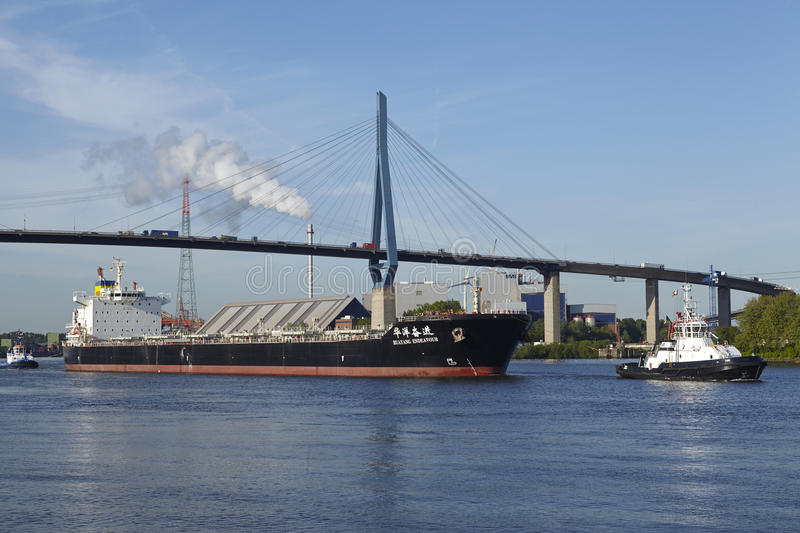 Hamburg - Freighter under Koehlbrand Bridge. The freighter Huyang Endeavour is accompanied of the tugboats Fair Play X and Turm under the Koehlbrand Bridge in stock photo