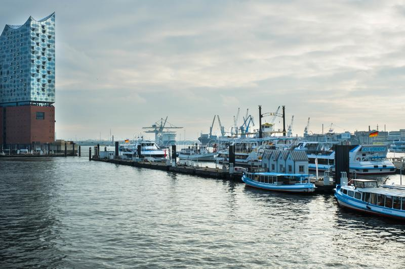 Hamburg. The harbor with piers and ships on the quay and a view of the Philharmonic standing on the bank of the Elbe royalty free stock photography