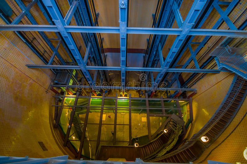 HAMBURG, GERMANY - JUNE 08, 2015: Old stain stairs behind elevators, blue structure and some lights on the way down stock photos