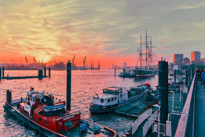 Hamburg, Germany - November 01, 2015: Ships towed at the quay of river Elbe attract unidentified tourists and visitors stock images