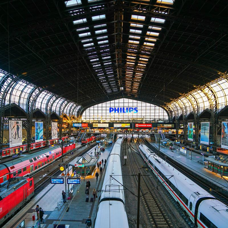 Hamburg Hauptbahnhof railway station. Hamburg Hauptbahnhof wide interior with elevate view of trains, people traveling and huge Philips advertisement. It is one royalty free stock images