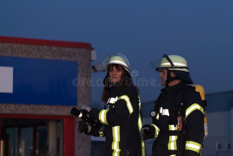 Hamburg Niemcy, Kwiecień, - 18, 2013: HDR - strażak i strażak w akci z firehose zdjęcie stock