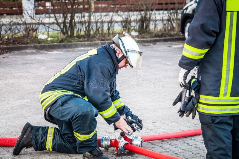 Hamburg Niemcy, Kwiecień, - 18, 2013: HDR - strażak w akci i łączy dwa pożarniczego węża elastycznego obrazy royalty free