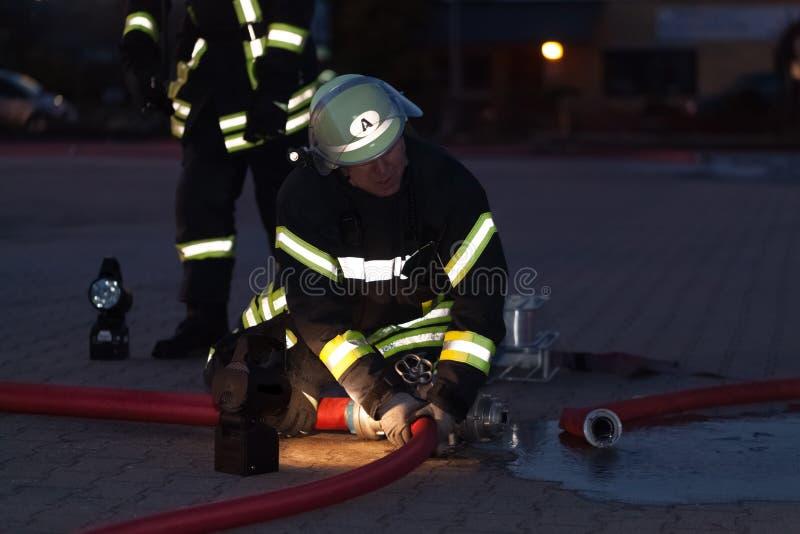 Hamburg Niemcy, Kwiecień, - 18, 2013: HDR - strażak w akci z pożarniczym wężem elastycznym w wieczór obrazy royalty free