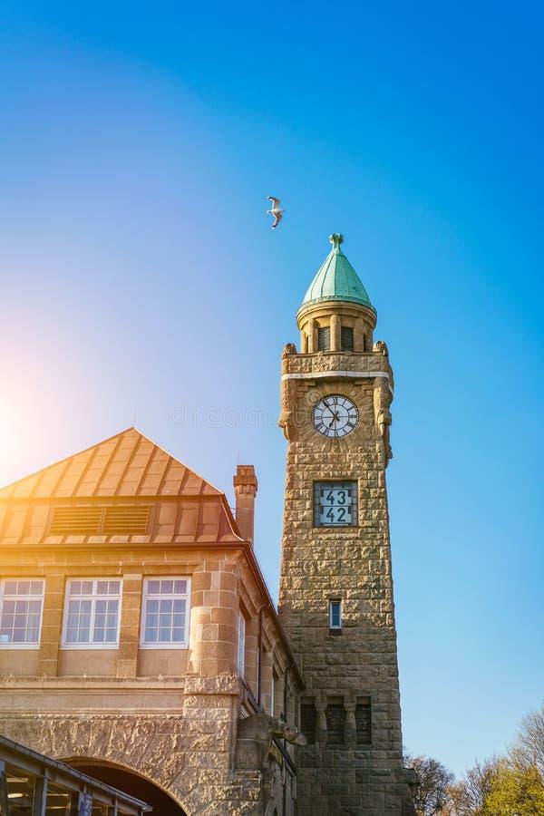 Hamburg Tyskland - Maj 17, 2018: Klockatorn av den berömda hamburgaren Landungsbruecken med den kommersiella hamnen och Elbe arkivfoto