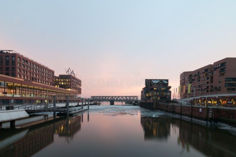Hamburg Tyskland - mars 04, 2014: Sikt från den Busan bron i Hafencity Hamburg på den Magdeburger bron i aftonen arkivfoto