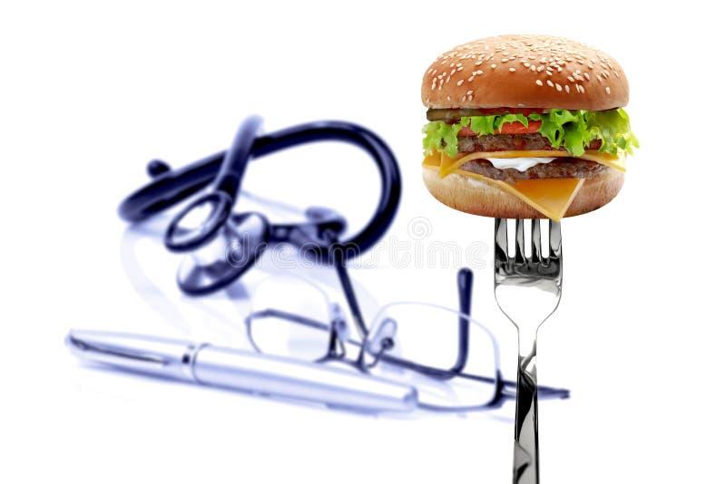 Hamburgare, exponeringsglas, en penna och stetoskop på den vita bakgrunden arkivfoton