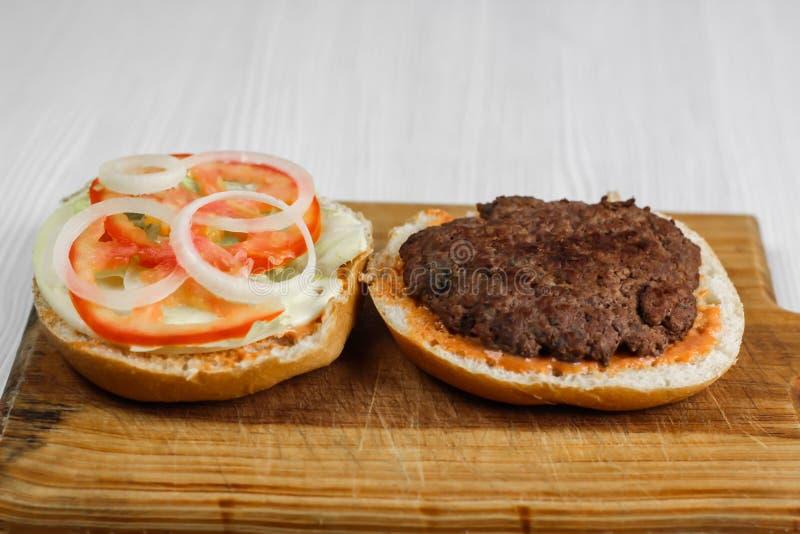 Hamburgare för malt nötkött med tomaten, löken och grönsallat som är hemlagade royaltyfri fotografi