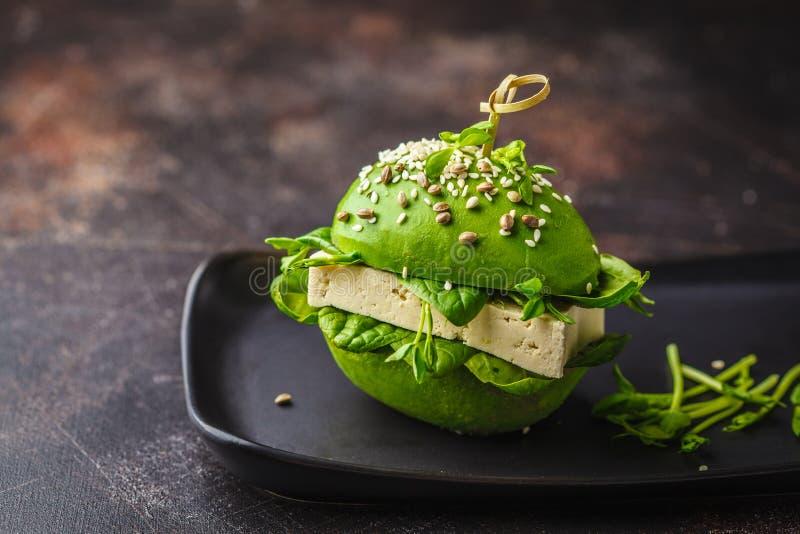 Hamburgare för strikt vegetarianavokadotofu på svart maträtt Sund detoxmat, växt baserade matbegrepp royaltyfria foton