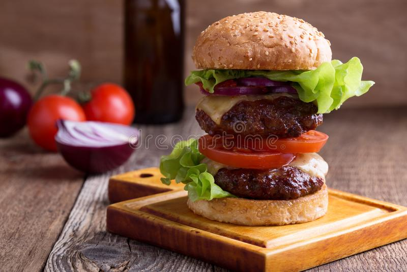 Hamburgare för två liten pastej med grönsallat, ost tomat och röd lök royaltyfria bilder