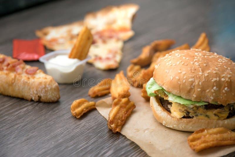 Hamburgare franska småfiskar lyx-, pizza-, ost-, grönsallat- och gräddfilsås royaltyfri fotografi