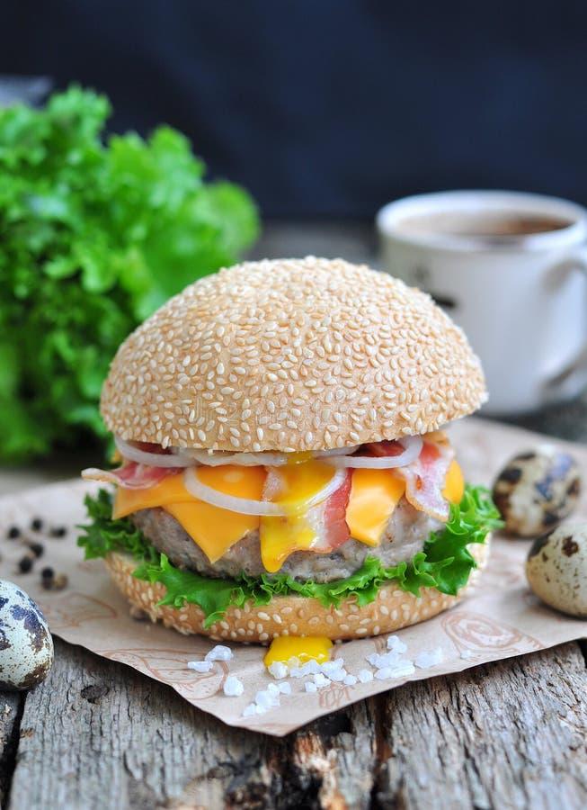 Hamburgare, hamburgare med grillat nötkött, ägg, ost, bacon och grönsaker royaltyfri fotografi