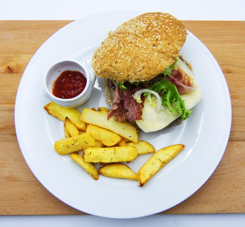 Hamburgare med grönsallat och ost, småfiskar och ketchup, på trätabellen arkivfoto