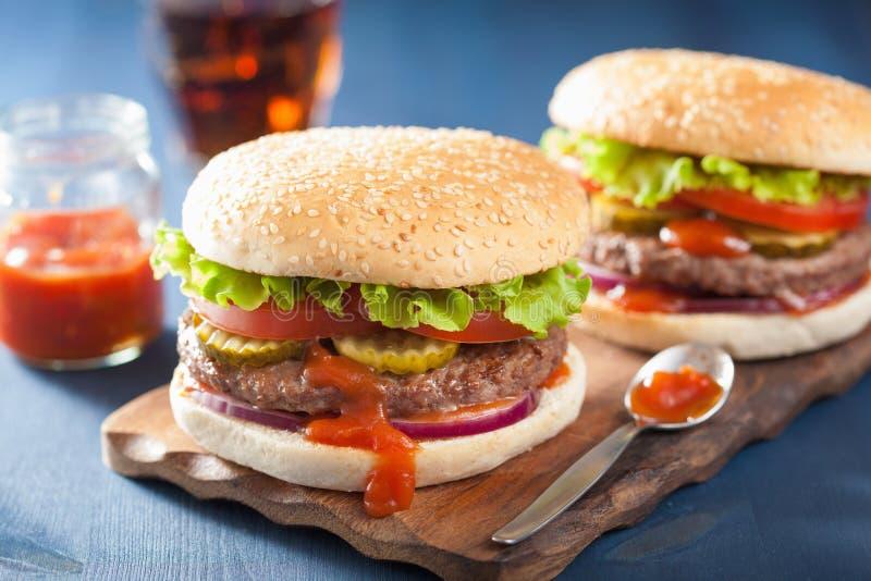 Hamburgare med ketchup för tomat för lök för grönsallat för nötköttliten pastej arkivfoton