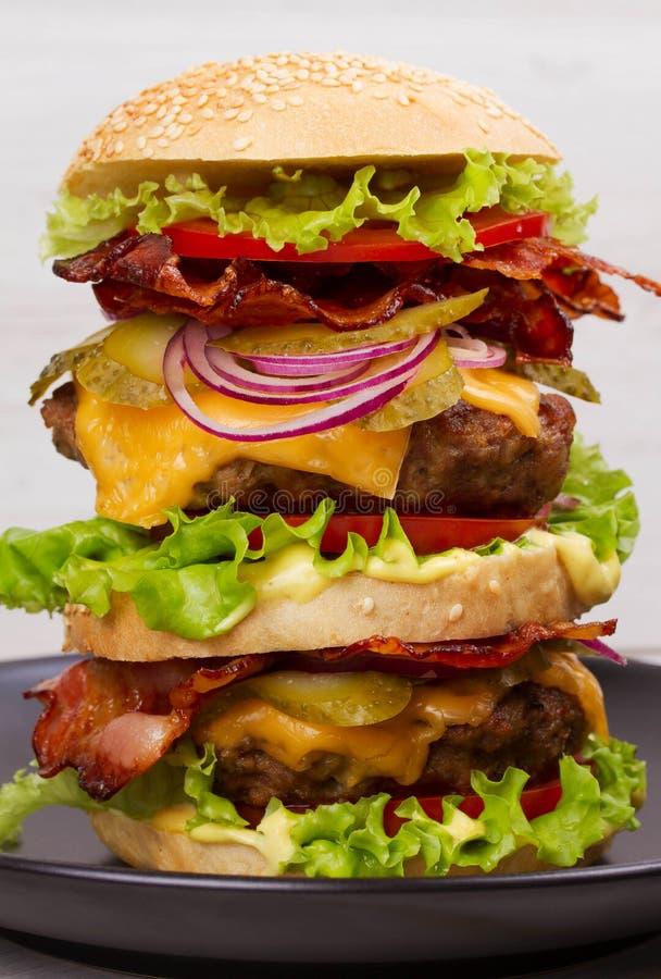 Hamburgare med nötkött, bacon, tomaten, ost, grönsallat och löken royaltyfria bilder