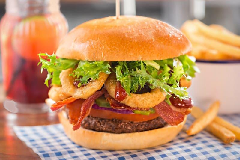 Hamburgare med nötkött, tomaten, löken, knipor, bacon, lökcirklar, grönsallat och grillfestsås arkivbild