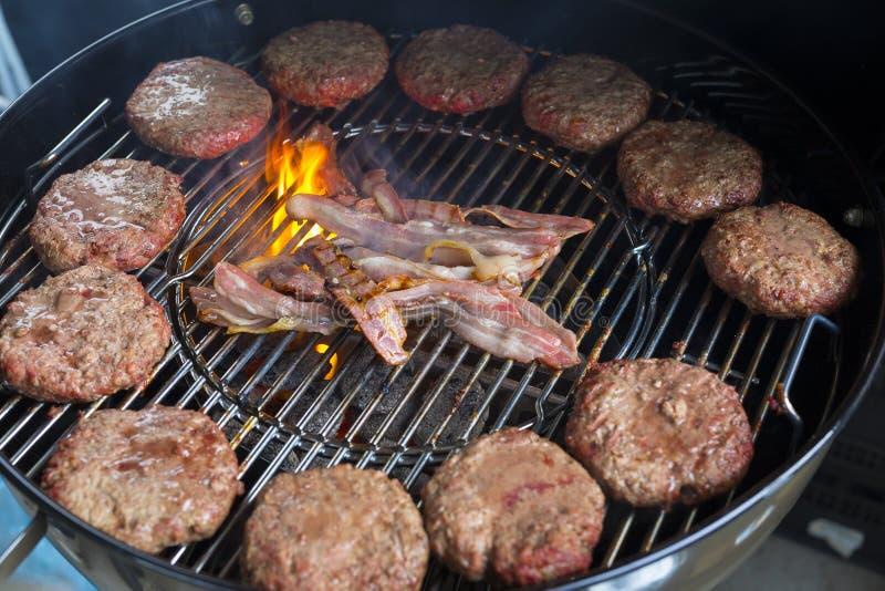 Hamburgare och bacon på ett varmt galler med brand royaltyfri fotografi