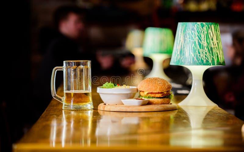 Hamburgare och franska småfiskar och tomatsås på träbräde läcker hamburgare Hamburgare med ostkött och sallad pub royaltyfria foton