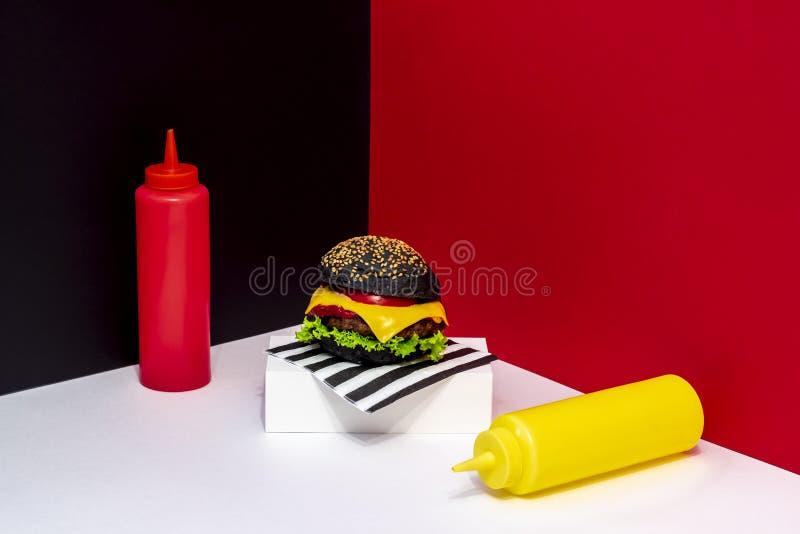 Hamburgare på en vit ställning R?d svartvit bakgrund minimalism id?rik mat Restaurangdesign royaltyfria bilder