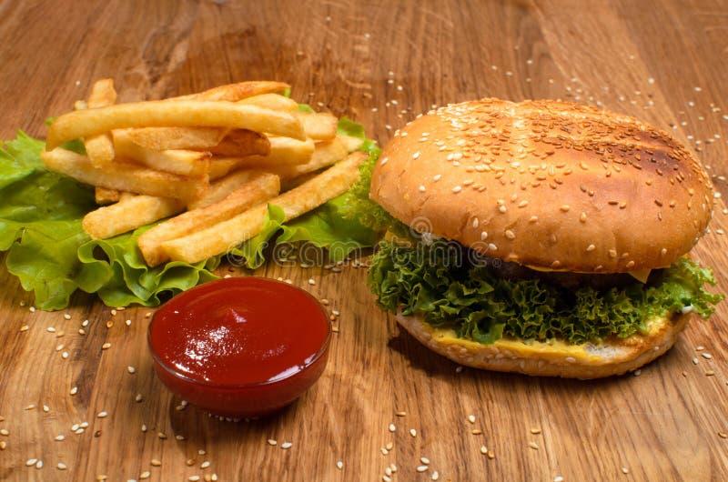 Hamburgare p? tr?tabellen med franska sm?fiskar L?ckert m?l med ketchup fotografering för bildbyråer