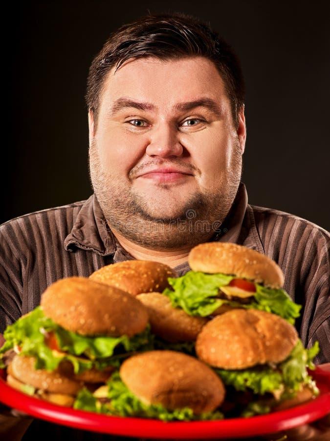 Hamburgare som äter den feta mannen för snabbmatstrid som äter snabbmat royaltyfria foton