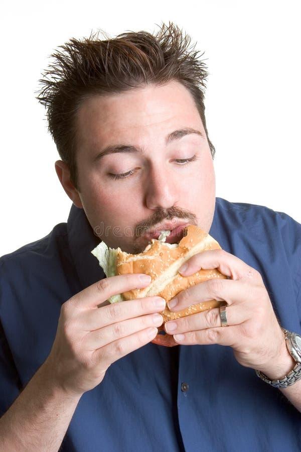 hamburgare som äter mannen royaltyfria bilder