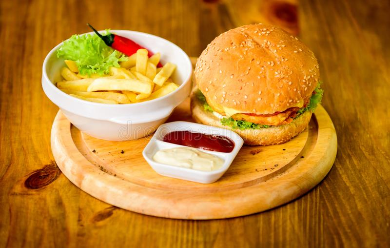 Hamburgaremeny Högt kalorimellanmål Hamburgare och franska småfiskar och tomatsås på träbräde Pommes frites-, hamburgare- och ket royaltyfri foto