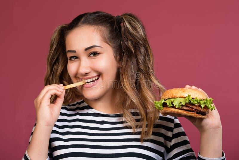 hamburgaren äter kvinnan Slut upp framsidaståendeflicka med snabbmat royaltyfria bilder