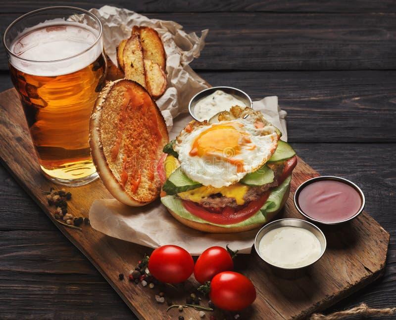 Hamburgaren och potatisar tjänade som med öl på restaurangen royaltyfri bild