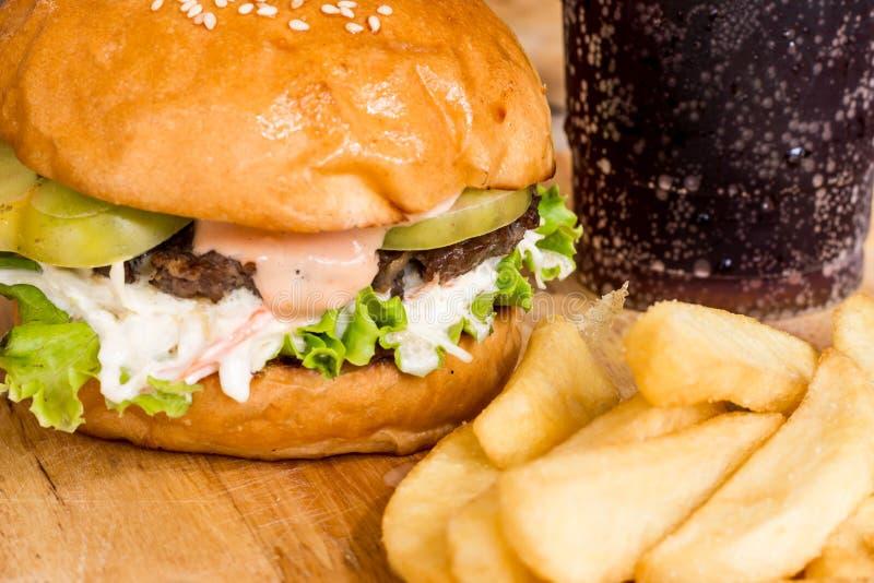 Hamburgerów i francuza dłoniaki na drewnie zdjęcie royalty free