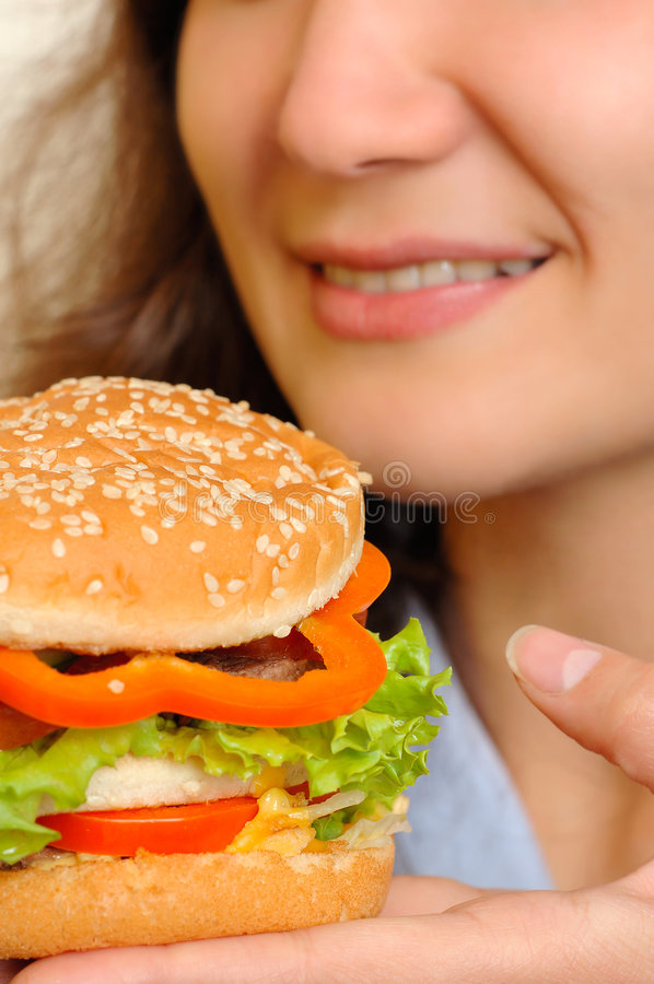 Hamburger. Young woman eating colorful appetizing hamburger stock photos