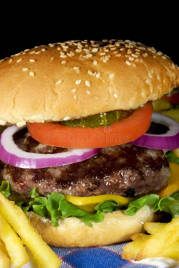 Hamburger. A grilled beef hamburger with lettuce, tomato, cheddar cheese, pickles, onions and topped with a sesame seed bun with crisp hot french fries along stock image