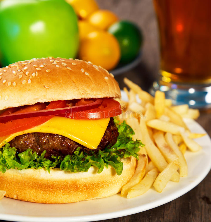 Hamburger. Fries and a glass of beer on a table. Close up