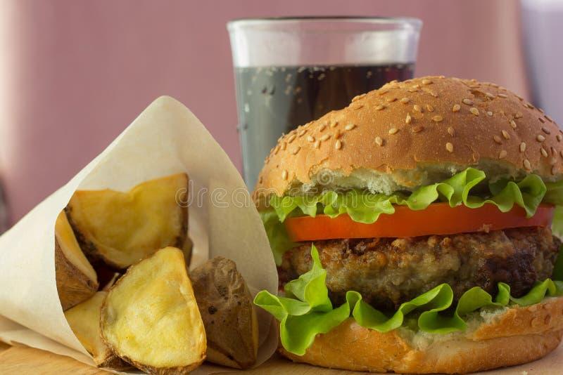 Hamburger, aardappelwiggen en kola op houten plaat stock foto