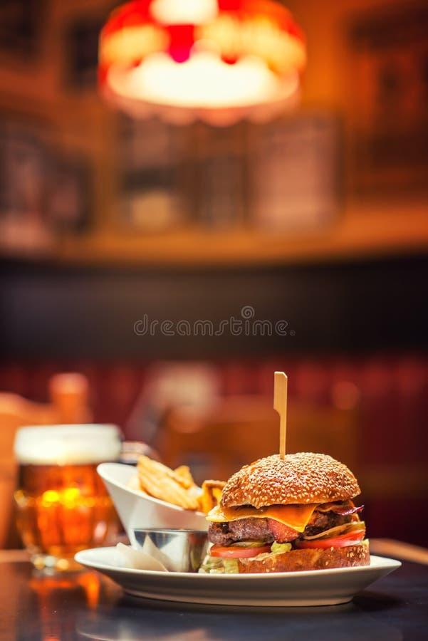 Hamburger américain avec le verre de bière ou de vin dans le restaurant, la bière, l'hamburger, le vin et d'autres specialites am images stock