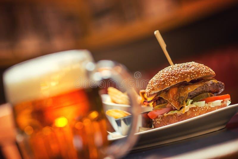 Hamburger américain avec le verre de bière ou de vin dans le restaurant, la bière, l'hamburger, le vin et d'autres specialites am photographie stock libre de droits