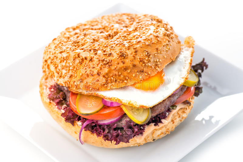 Hamburger américain original délicieux avec du boeuf, l'oeuf et les légumes grillés du plat, du casse-croûte ou du déjeuner blanc image stock