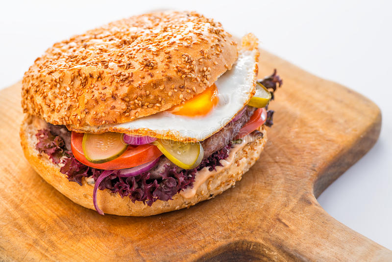 Hamburger américain original délicieux avec du boeuf, l'oeuf et les légumes grillés du plat, du casse-croûte ou du déjeuner blanc photos stock