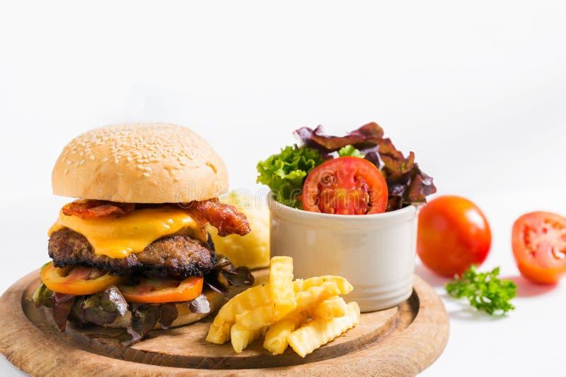 Hamburger arrostito saporito del manzo con lattuga sul piatto di legno fotografia stock libera da diritti