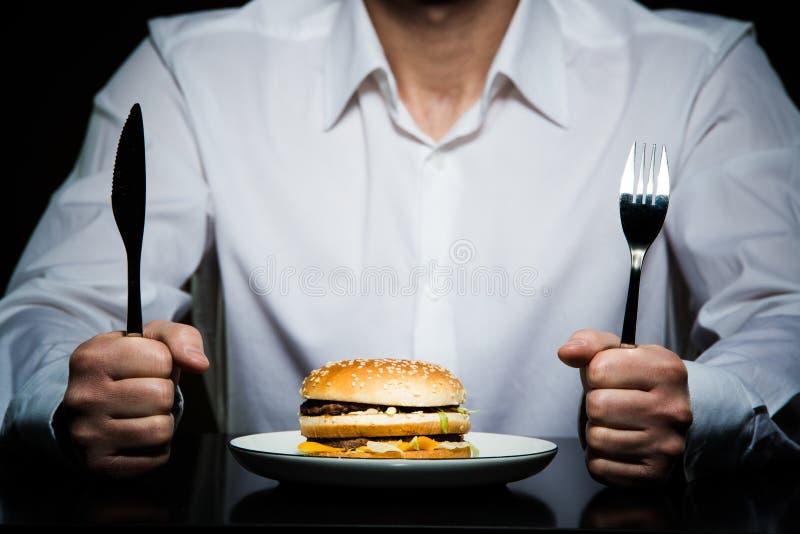 Hamburger auf einer Platte vor einem Mann stockfotografie