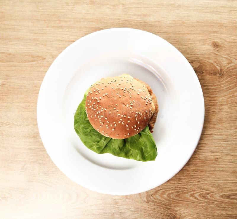 Hamburger auf einer weißen Platte auf hölzernem Hintergrund lizenzfreie stockbilder