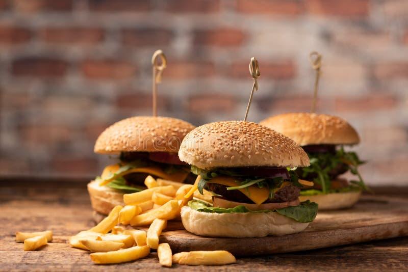 Hamburger avec de la laitue, fromage de cheddar, oignons, tomate photographie stock