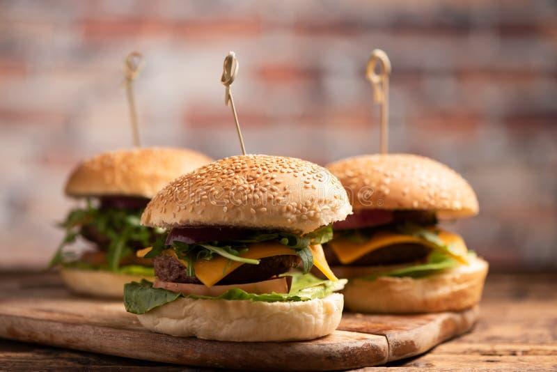 Hamburger avec de la laitue, fromage de cheddar, oignons, tomate images stock
